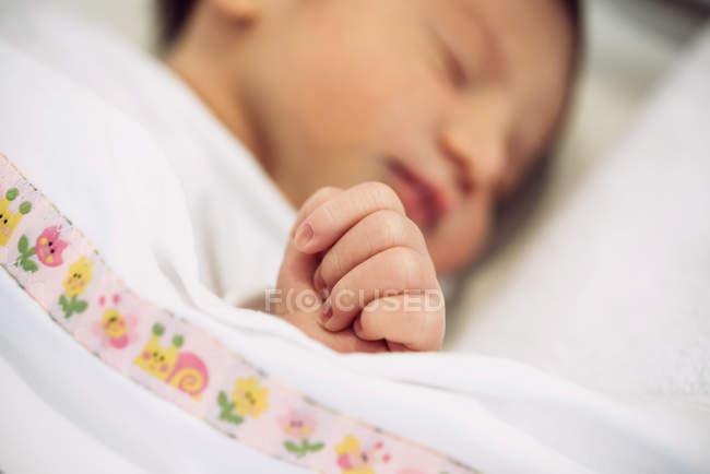 Neonato ragazza dormire sotto coperta con coperta modello floreale — Foto stock