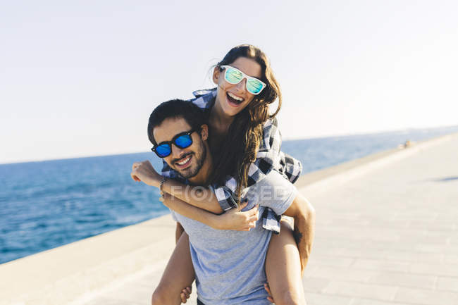 Portrait of smiling young couple piggybacking on harbor — Stock Photo
