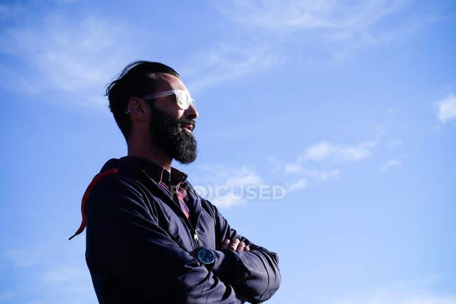 Portrait d'homme avec pleine barbe et lunettes de soleil debout devant ciel — Photo de stock