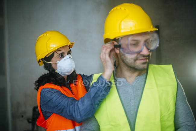 Woman helping a man to put on security glasses in the work. — Stock Photo