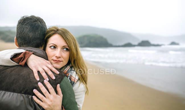 Испания, Астурия, Портрет женщины, смотрящей в сторону, в то время как мужчина на пляже зимой — стоковое фото