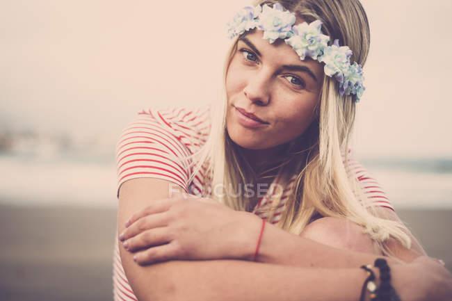 Портрет молодої жінки носять квіти, сидячи на пляжі — стокове фото