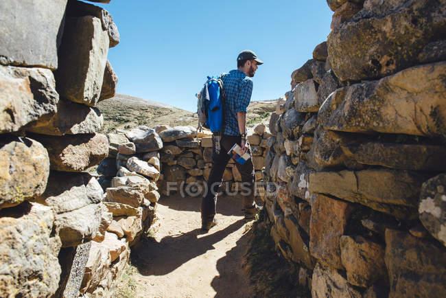 Isla del sol, Titicaca lake, Bolivia. Man with backpack and guidebook walking among the Chinkana ruins — Stock Photo