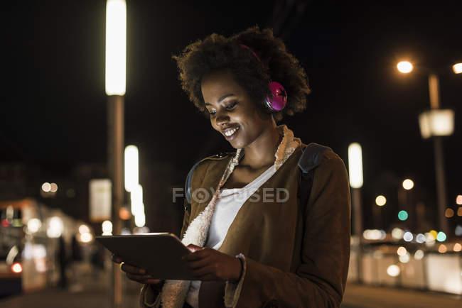 Mujer joven con tablet y auriculares esperando en la parada del tranvía - foto de stock