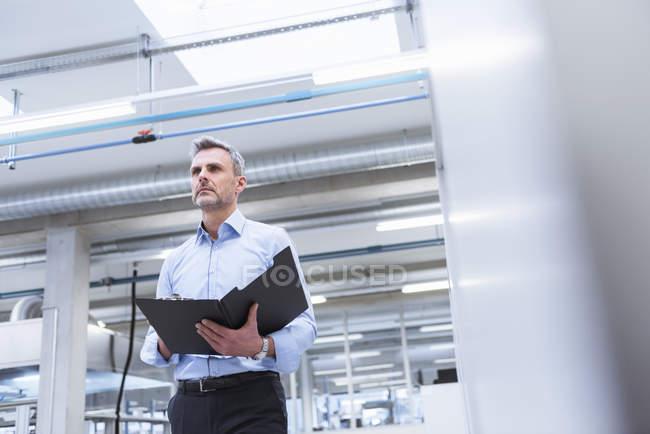 Менеджер, стоя в фабрике — стоковое фото