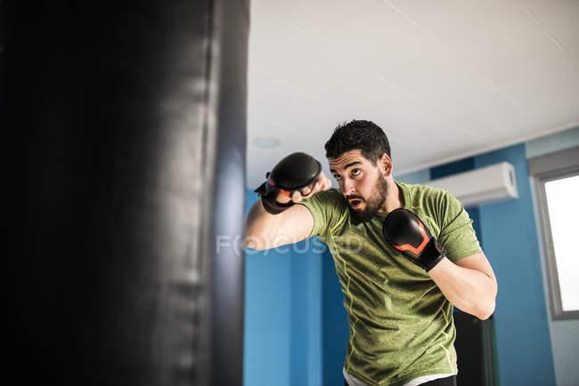 Sportliche kaukasischen Boxer trainieren mit Boxsack — Stockfoto