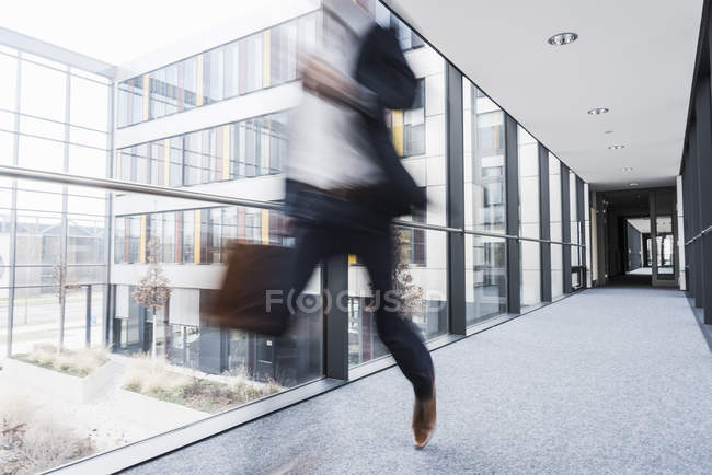 Blurred view of businessman running in hallway — Stock Photo