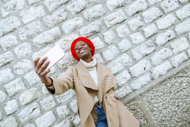 Frau, die Selfie vor Backsteinmauer — Stockfoto