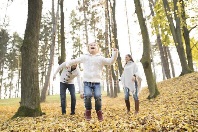 Menina feliz com a família na floresta outonal — Fotografia de Stock