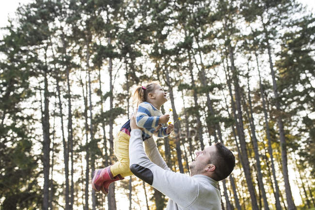 Father lifting up his daughter in forest — Stock Photo
