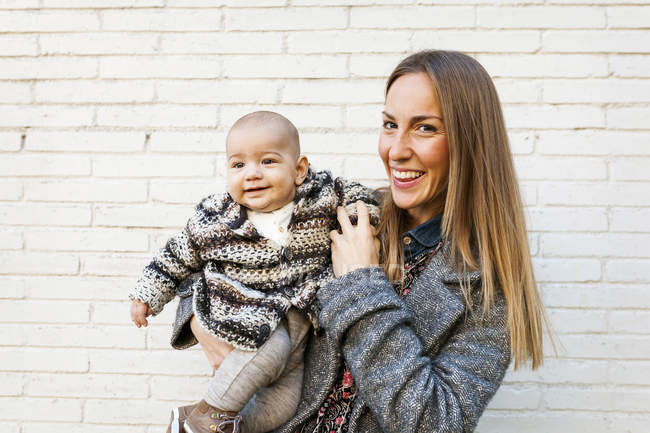 Portrait of young woman holding baby boy — Stock Photo
