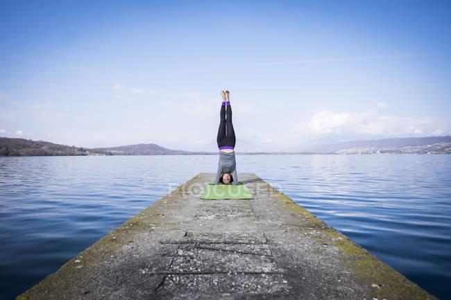 Pratica yoga facendo un headstand su un molo in un lago della donna — Foto stock