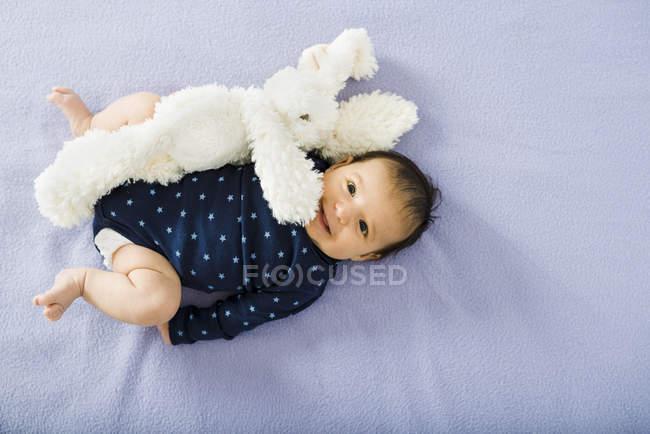 Menina feliz bebê recém-nascido, deitado na cama com um coelho de peluche — Fotografia de Stock