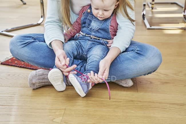 Матір та дитинча дівчина сидить на підлозі, пов'язуючи взуття — стокове фото