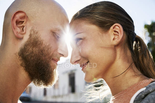 Young couple in love face to face at backlit — Stock Photo