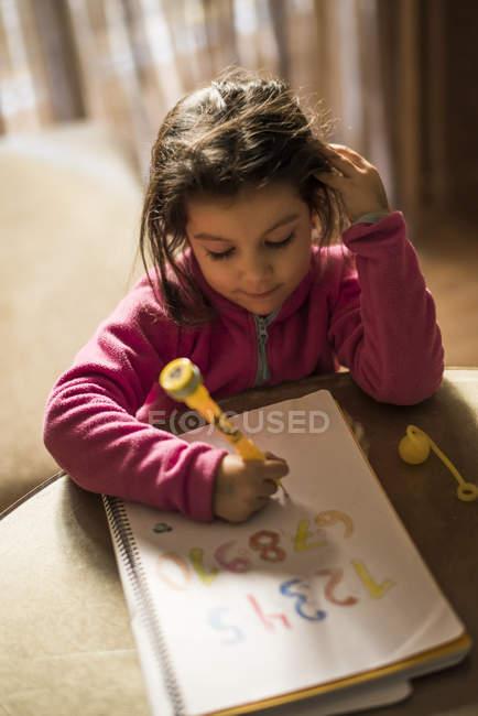 Petite fille studding numéros assis à la maison — Photo de stock