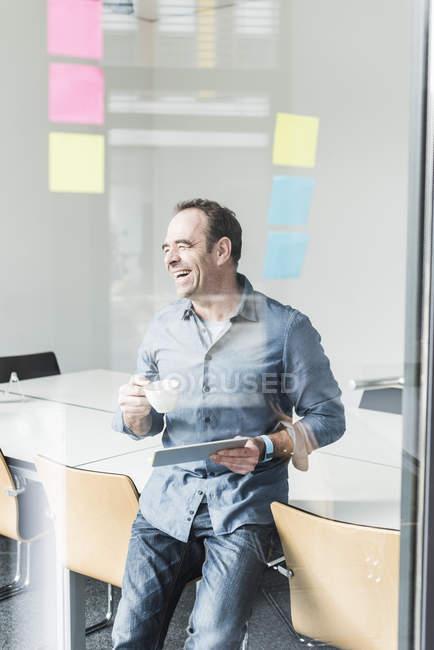 Портрет зрелого улыбающегося бизнесмена с планшетом — стоковое фото