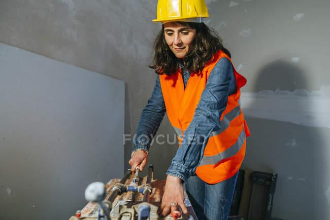 Женщина работает резки плитки на строительной площадке — стоковое фото