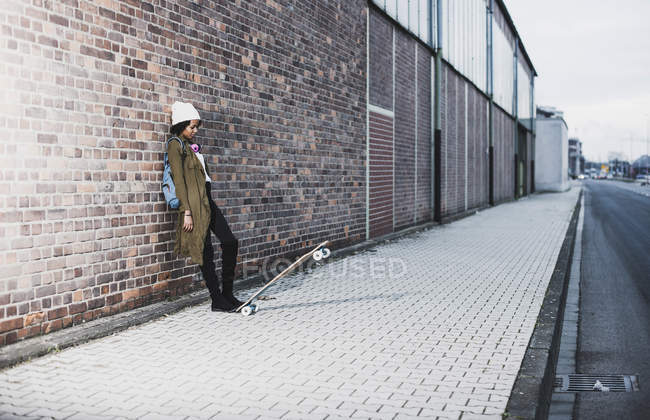 Young woman with headphones, backpack and skateboard leaning against brick wall — Stock Photo