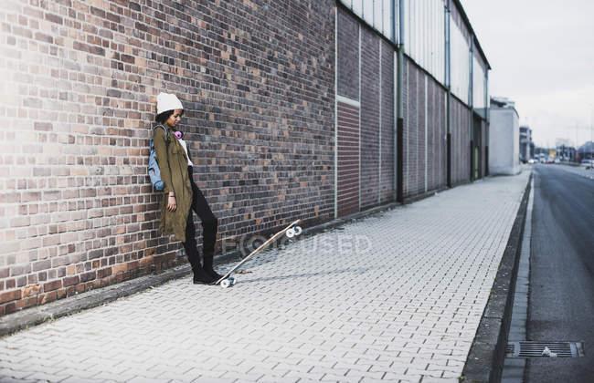 Giovane donna con le cuffie, zaino e skateboard che si appoggia contro il muro di mattoni — Foto stock