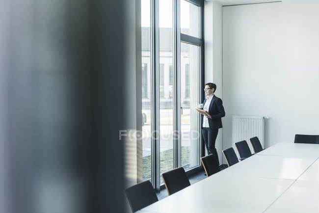 Portrait de femme d'affaires mature debout près de la fenêtre dans le bureau — Photo de stock