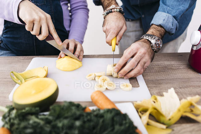 Hands slicing fresh fruits — Stock Photo