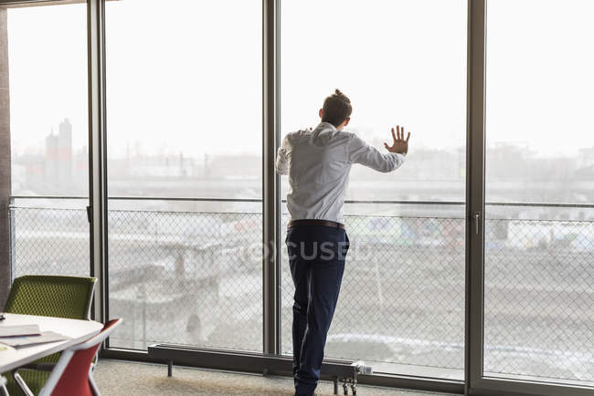 Portrait of businessman leaning on window glass — Stock Photo