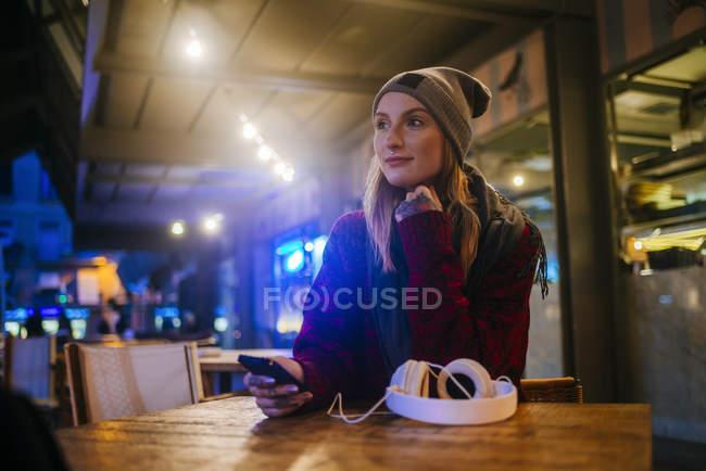 Jovem com um telefone móvel sentado no terraço de um bar . — Fotografia de Stock