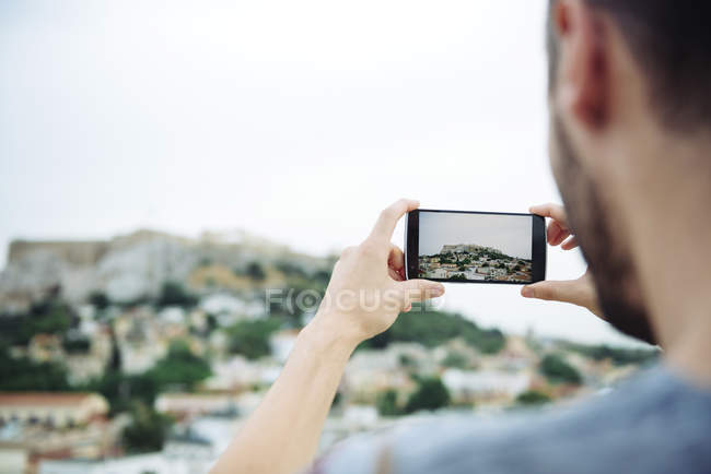 Athens, Greece. Man taking a photo with a smartphone of The Parthenon in the Athenian Acropolis surrounded by the city. — Stock Photo