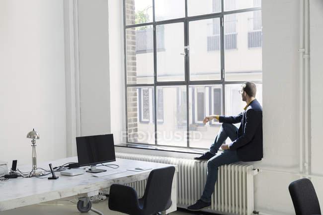 Jeune homme d'affaires regardant par la fenêtre dans le bureau — Photo de stock