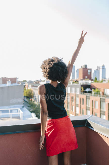 Portrait of young woman showing victory sign on roof terrace — Stock Photo