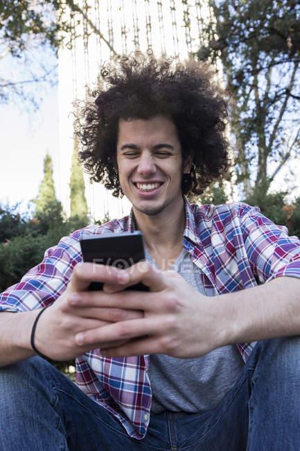 Jeune homme souriant utilisant un smartphone en ville — Photo de stock