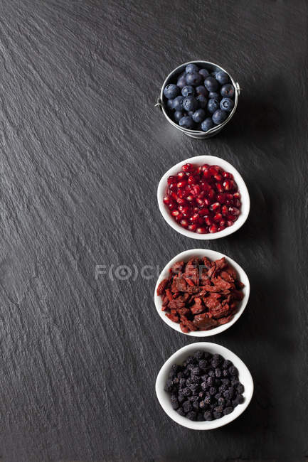 Top view of blueberries with pomegranate seeds, wolfberries and chokeberries in bowls — Stock Photo