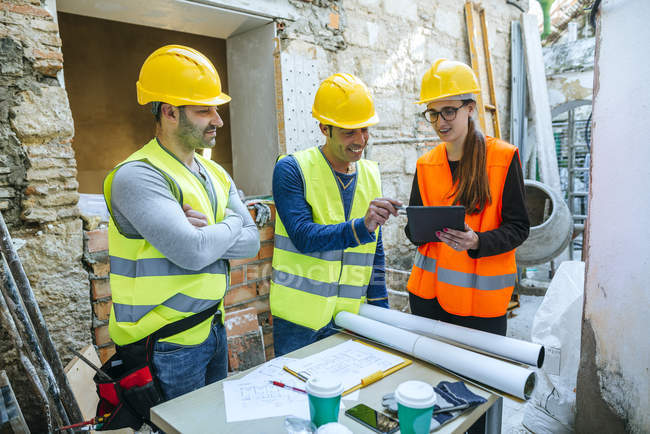 Group of workers talking about the project with a tablet. — Stock Photo