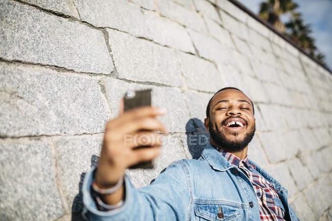 Giovane viaggiatore che fa autoritratto con cellulare . — Foto stock