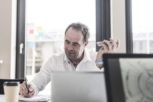 Portrait d'homme d'affaires senior holding smartphone et prendre des notes — Photo de stock