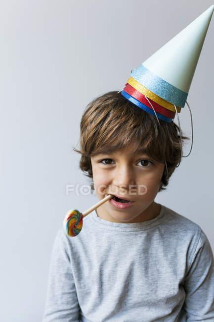 Портрет хлопчика в партії капелюх з льодяник в рот — стокове фото