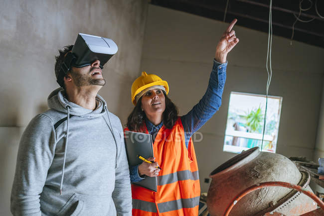 Working woman showing a man the house through a virtual reality glasses. — Stock Photo