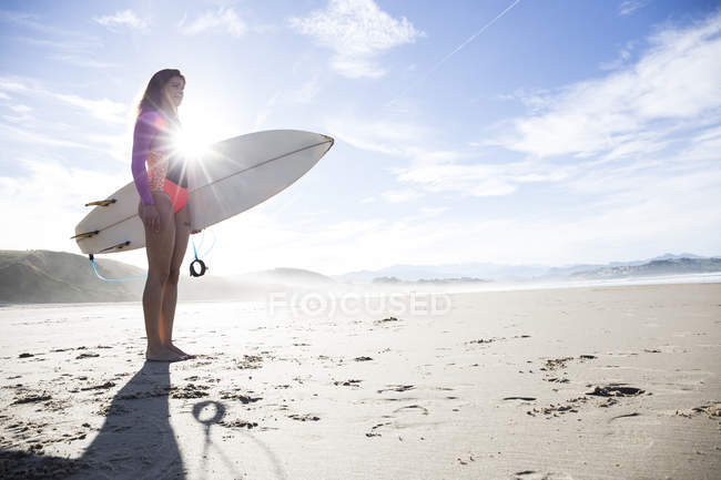 Young woman with surfboard standing on sandy beach in backlit — Stock Photo