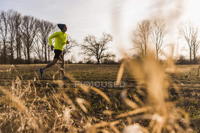 Портрет молодого человека, бегущего в поле — стоковое фото