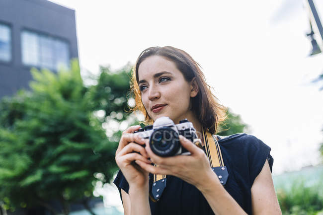 Woman holding old-fashioned camera in city — Stock Photo