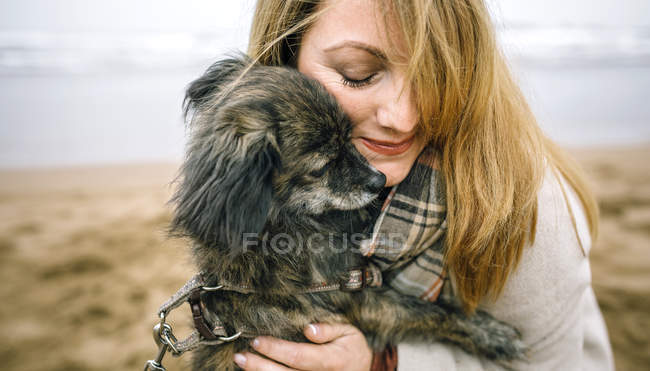 Close up of happy woman with scarf hugging her dog in the beach — Stock Photo