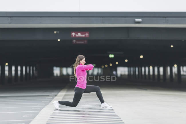 Young woman warming up before jogging — Stock Photo
