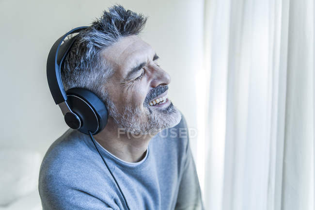 Portrait of smiling mature man listening music — Stock Photo