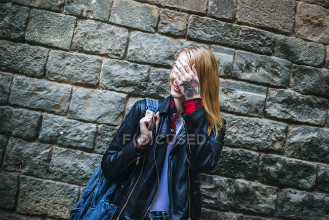 Portrait of tattooed woman covering her face with her hand — Stock Photo