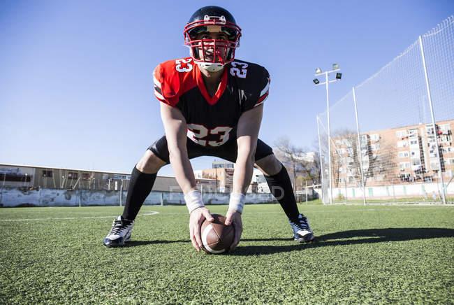 Американський футбол гравець з шолом і м'яч на спортивний майданчик — стокове фото