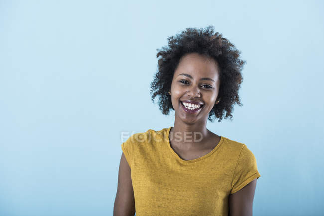 Portrait of happy young woman standing on blue background — Stock Photo
