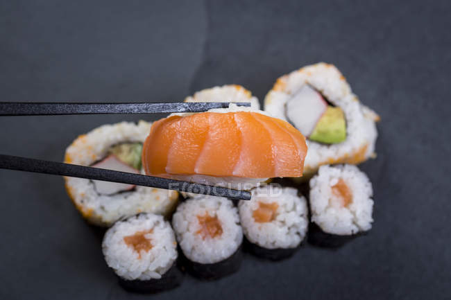 Closeup of chopsticks holding sushi, sushi set on dark background view — Stock Photo