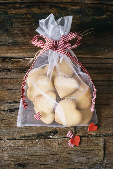 Bolsa de regalo de galletas en forma de corazón en madera con decoración - foto de stock