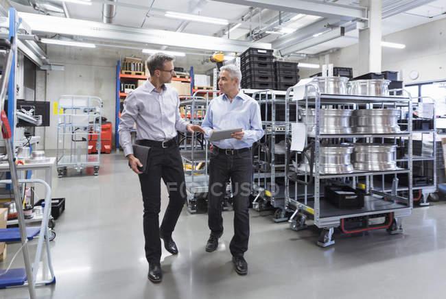Hommes d'affaires marchant dans le hall d'usine — Photo de stock